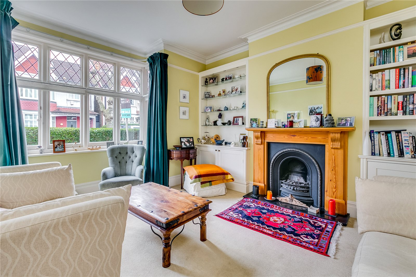 A fresh, brightly coloured rug draws attention to this fireplace's striking features.